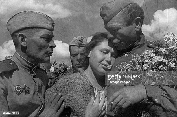 Victory day, World War II, USSR, 1945. A woman celebrating the defeat of Nazi Germany with members of the victorious Soviet Red Army. Found in the...