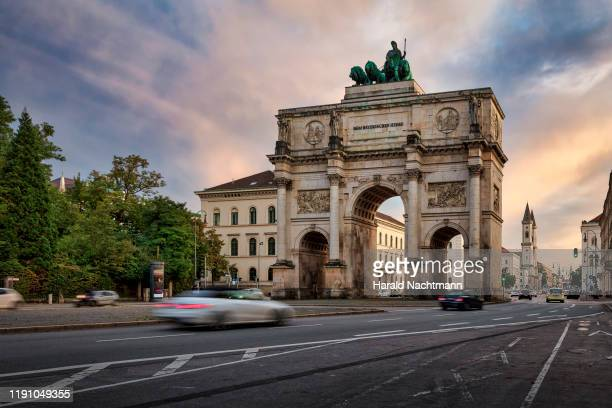 victory gate with city traffic, munich, bavaria, germany - münchen stock-fotos und bilder