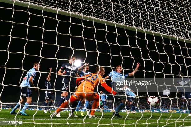 Victory goalkeeper Lawrence Thomas fails to stop a goal by Aaron Calver of Sydney FC as Rhyan Grant of Sydney FC plays for the ball during the...
