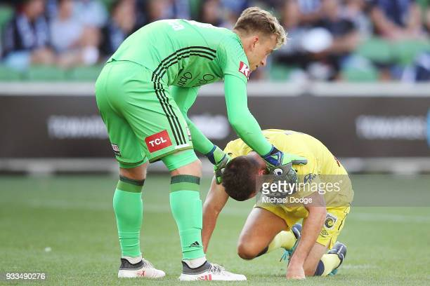 Victory goalkeeper Lawrence Thomas helps up Blake Powell of Central Coast Mariners who collided with Thomas Deng of the Victory in a contest for the...
