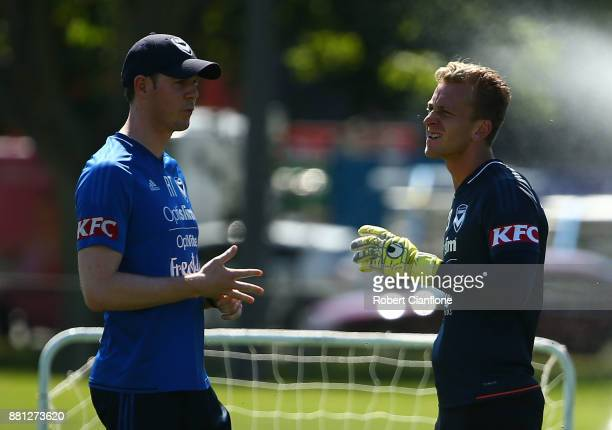 Victory goalkeeper Lawrence Thomas talks with physiotherapist Rees Thomas after sustaining an injury to his right hand during a Melbourne Victory...