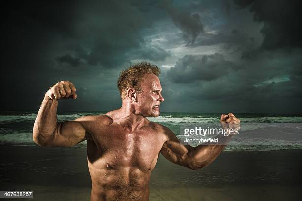 victory - muscle men at beach stock photos and pictures