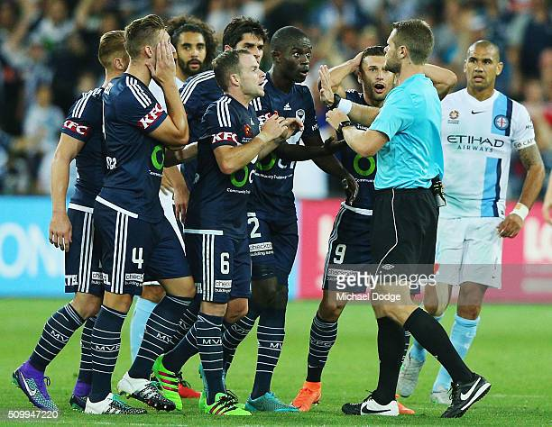 Victory players argue with the umpire after viewing a replay during the round 19 ALeague match between Melbourne City FC and Melbourne Victory at...