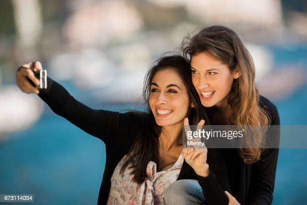 victory sign young women taking selfies together - mlenny stock pictures, royalty-free photos & images