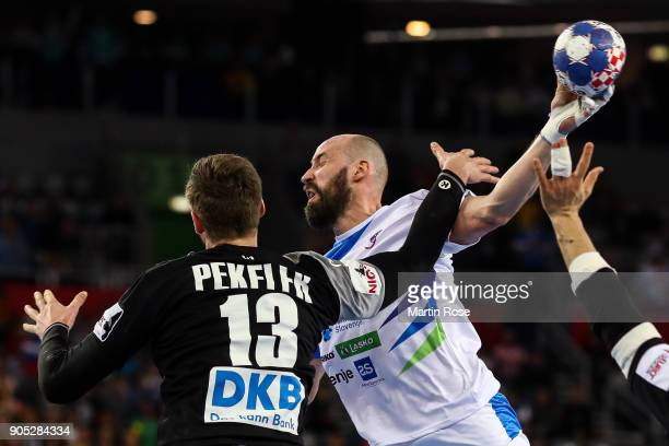 Vid Kavticnik of Slovenia is challenged by Hendrik Pekeler of Germany during the Men's Handball European Championship Group C match between Slovenia...