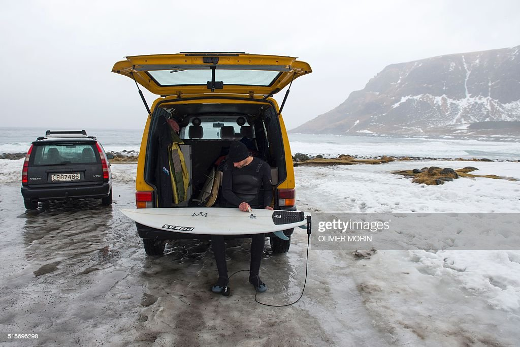 Vidar, a Norwegian surf instructor, waxes his board before going to the water to surf at the snow covered beach Unstad in Lofoten Island, Arctic Circle, on March 12, 2016. Surfers from all over the world come to Lofoten island to surf in extrem conditions. Ocean temperature is 5-6 °C, air temperature around 0°C in spite of a weather very unstable. / AFP / OLIVIER