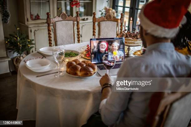 video call on a christamas dinner - coronavirus winter stock pictures, royalty-free photos & images