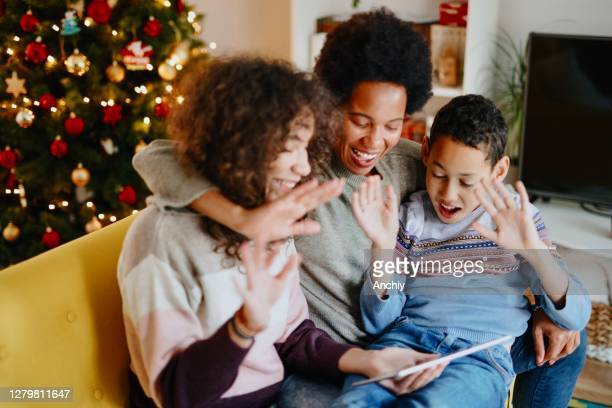 video call with family on christmas day during pandemic - christmas family stock pictures, royalty-free photos & images