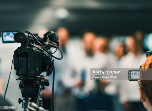 video camera against people in event - journalist stock pictures, royalty-free photos & images