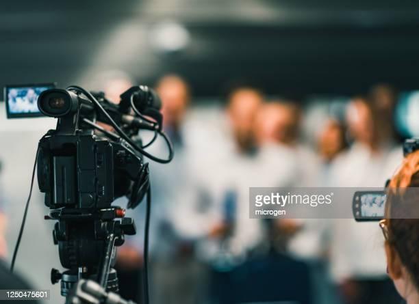 video camera against people in event - pressekonferenz stock-fotos und bilder