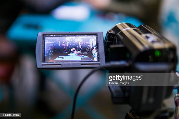 video camera is recording a man and a woman during an interview - ルポルタージュ ストックフォトと画像