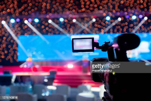 video camera operator working with his equipment at indoor event. cameraman silhouette at meeting room - television show stock-fotos und bilder