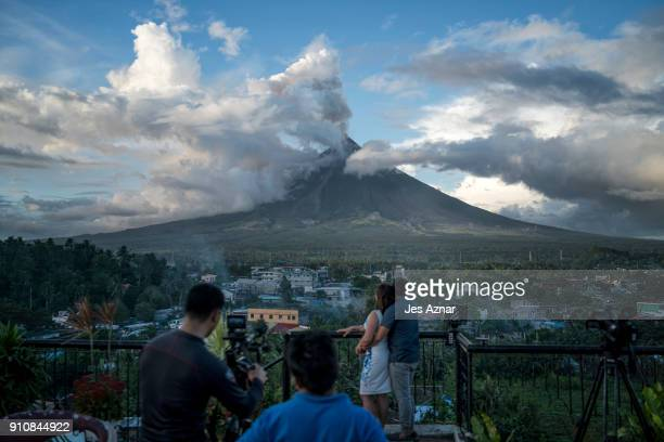 A video crew films a couple overlooking Mayon volcano as it spews ash and lava on January 26 in Albay Philippines Over 70000 villagers have been...