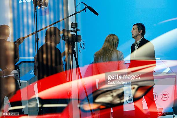 A video crew is seen behind a reflection of an image of a Ford Focus in a window at the twoday media preview event for the 2010 Los Angeles Auto Show...