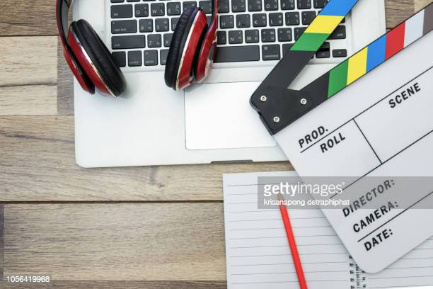 video editing,office stuff with movie clapper laptop - ディレクター ストックフォトと画像