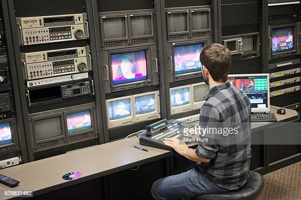 Video editor at work in a TV editing control room at a Cable TV Studio