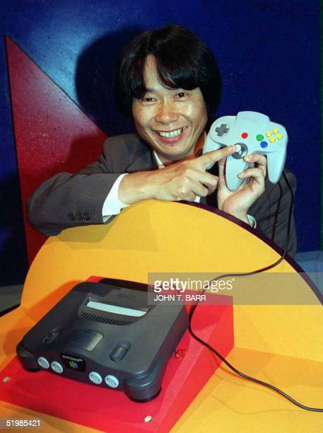 Video game designer, Shigeru Miyamoto from Japan, points to the handset of the new Nintendo 64 flagship game, Super Mario 64, at the Los Angeles...