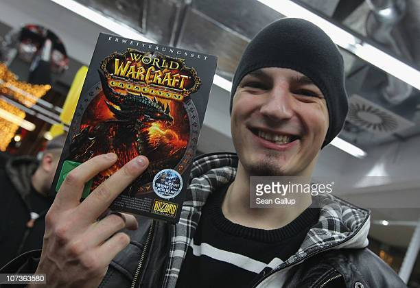 A video gaming enthusiast holds up his copy of the new 'World of Warcraft Cataclysm' game shortly after midnight at the game's global sales premiere...