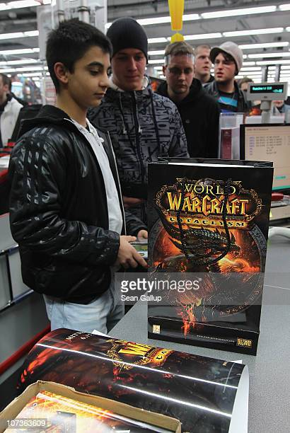 Video gaming enthusiasts buy the new 'World of Warcraft Cataclysm' game shortly after midnight at the game's global sales premiere at MediaMarkt on...