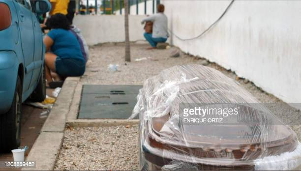 A video grab from AFP TV shows a wrapped coffin on the sidewalk outside of a hospital in Guayaquil Ecuador on April 1 2020 Residents of Guayaquil in...
