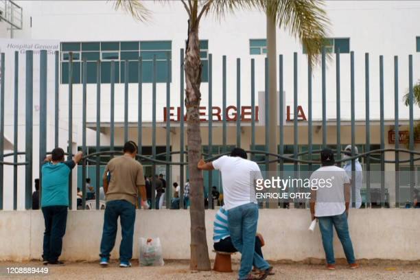 A video grab from AFP TV shows relatives waiting outside of a hospital for information on family members infected with Covid19 in Guayaquil Ecuador...