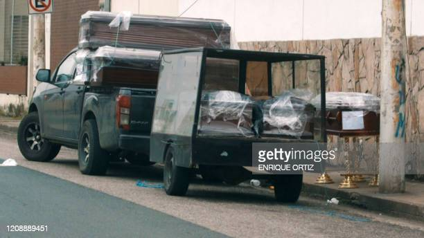A video grab from AFP TV shows wrapped coffins on the back of a pickup truck on the sidewalk outside of a hospital in Guayaquil Ecuador on April 1...