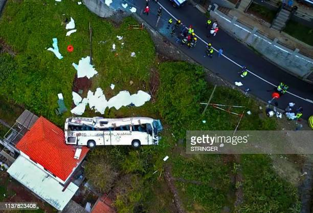 TOPSHOT A video grab obtained from drone footage shows the wreckage of a tourist bus that crashed on April 17 2019 in Canico on the Portuguese island...