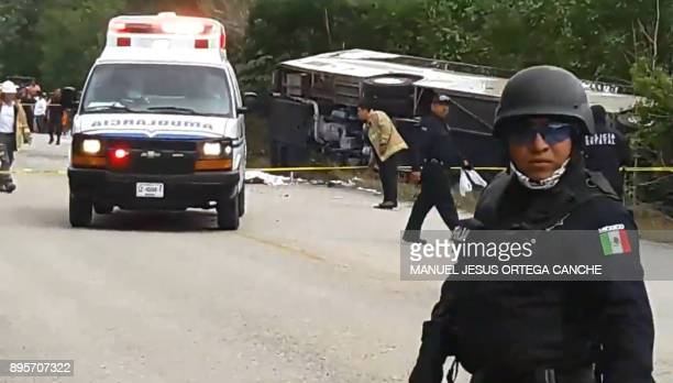 Video grab of Mexican police officers standing guard in the area where a bus driving tourists to Chacchoben archaeological zone overturned in the...