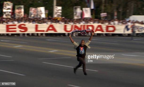 VIdeo grab showing a man who burst in front of the May Day march waving a US flag at Revolution Square in Havana on May 1 2017 / AFP PHOTO / AFPTV /...
