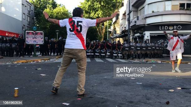 Video grab showing a supporter of River Plate gesturing at riot police in the surroundings of the Monumental stadium in Buenos Aires following an...