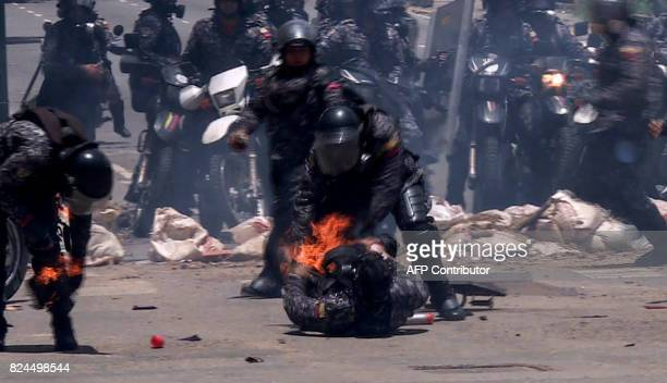 Video grab showing police officers helping a colleague who caught fire after an explosive device went off as they rode past during a protest against...