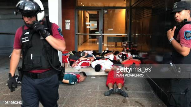 TOPSHOT Video grab showing security forces arresting guarding detained supporters of River Plate during clashes in the surroundings of the Monumental...