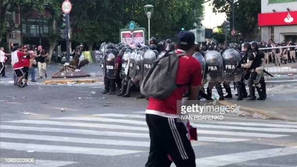 Video grab showing supporters of River Plate clashing with riot police in the surroundings of the Monumental stadium in Buenos Aires following an...