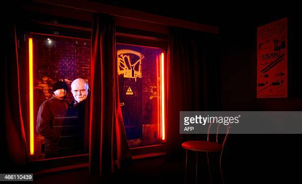 A video installation shows men taking a look inside a brothel at 'Red Light Secrets' the first Museum of Prostitution in Amsterdam The Netherlands on...
