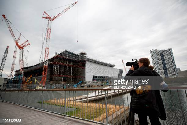 A video journalist films the under construction Ariake Arena venue for volleyball at the Tokyo 2020 Olympic Games and wheelchair basketball in the...