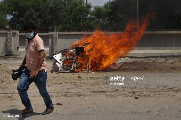 Video journalist walks past the burned chinese products during a protest against Chinese President Xi Jinping in Gurugram on the outskirts of New...