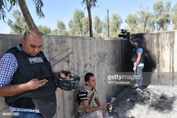 Video journalists take cover behind a wall amid fighting in the region of Altun Kupri about 50 kilometres from Arbil the capital of autonomous Iraqi...