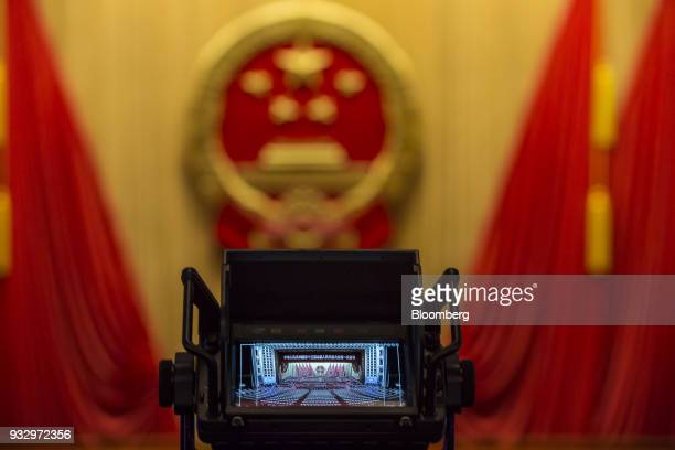 A video monitor showing the Great Hall of the People is displayed ahead of a session during the first session of the 13th National People's Congress...