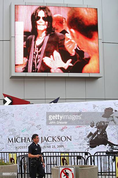 Video monitor stands above a poster signed by fans at the Michael Jackson public memorial service at Staples Center on July 7, 2009 in Los Angeles,...
