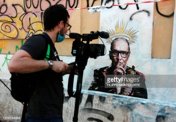 Video reporter films a mural by street artist Harry Greb depicting late Italian music composer Ennio Morricone, which has appeared in Rome a day...