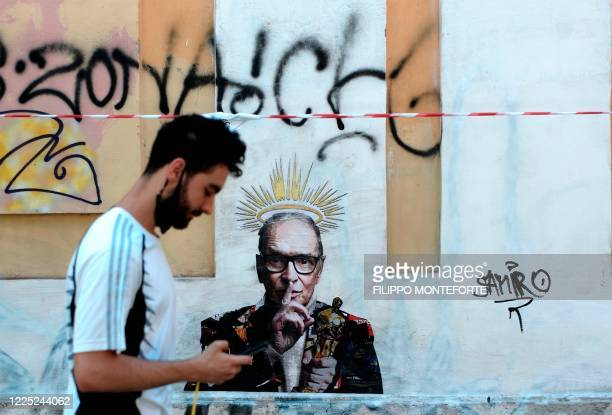 Video reporter stands by a mural by street artist Harry Greb depicting late Italian music composer Ennio Morricone, which has appeared in Rome a day...