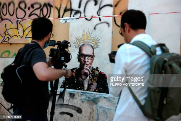 Video reporters film a mural by street artist Harry Greb depicting late Italian music composer Ennio Morricone, which has appeared in Rome a day...