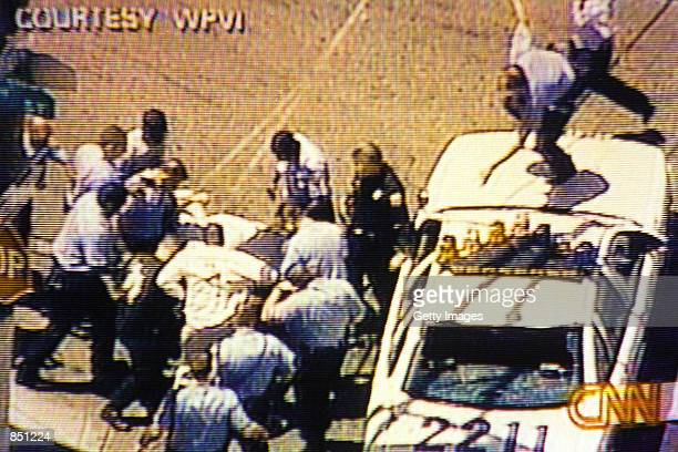 Video still of Philadelphia Police pulling a suspect out of a car and beating him on July 7 2000 in Philadelphia PA The suspect shot at police...