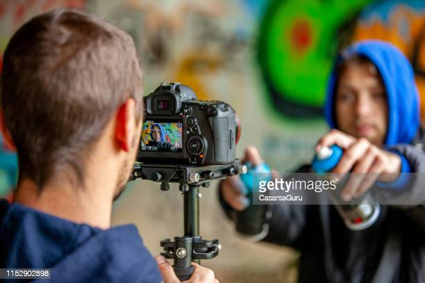 videographer filming graffiti artist - street artist stock pictures, royalty-free photos & images