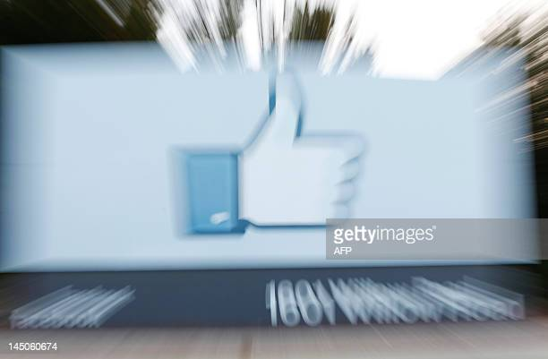 Videographer shoots the side of Facebook's Like Button logo displayed at the entrance of the Facebook Headquarters in Menlo Park, California as...