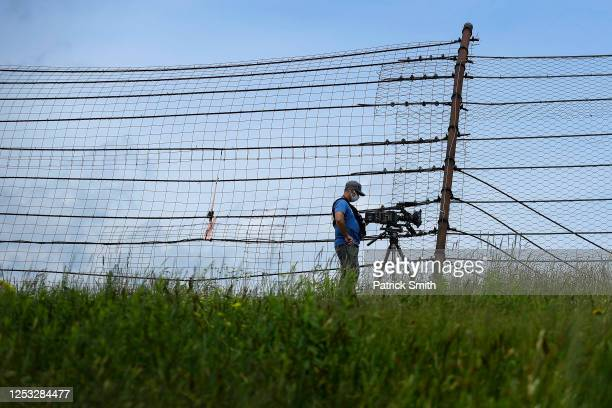 Videographer wears a face covering as he photographs the NASCAR Xfinity Series Pocono Green 225 Recycled by J.P. Mascaro & Sons at Pocono Raceway on...