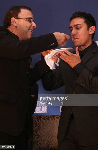 Vidhu Vinod Chopra gives Aamir Khan a piece of his birthday cake at the dinner party hosted after the India Today Conclave ended in New Delhi on...