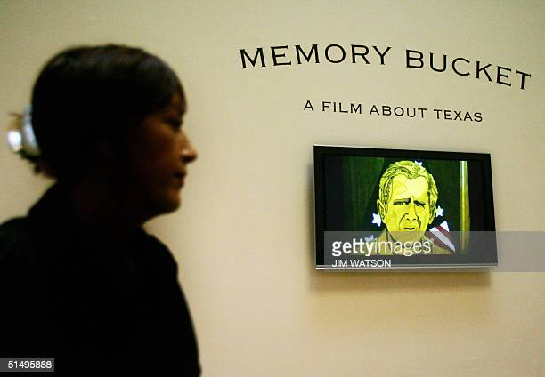 A vidoe of US President George W Bush pops up on screen as a woman sits watching shortlisted artist Jeremy Deller's documentary 'Memory Bucket' which...