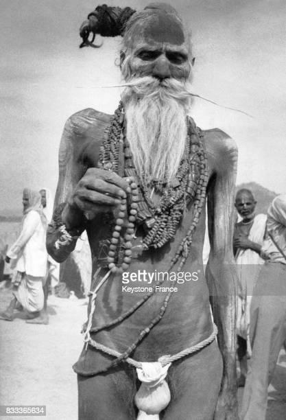 Vieil homme dénudé portant une très longue barbe et de nombreux colliers participe au festival Kumbh Mela à Haridwar Inde