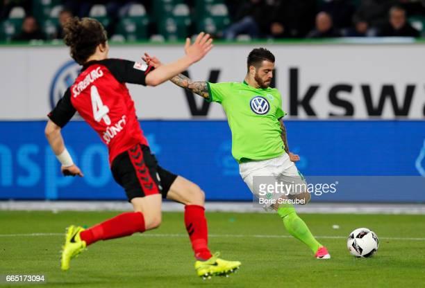 Vieirinha of VfL Wolfsburg is challenged by Caglar Soeyuencue of Freiburg during the Bundesliga match between VfL Wolfsburg and SC Freiburg at...